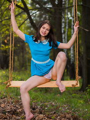 Hilary C playfully poses outdoors baring her slender body on the swing.