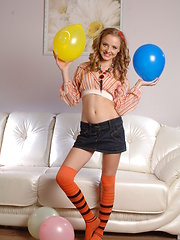 Beautiful shapely teen honey with colorful balloons taking off her clothes on the sofa