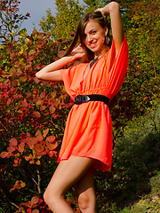 A smiling and confident Sofy frolics among the grass and plants in her bright orange dress like a carefree forest nymph.