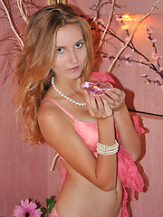 Beautiful honey stripping sexy pink lingerie and showing alluring slim body on the bed.