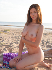 Irresistible busty girl gets some sand on that flawless shaved pussy of hers as she poses on the beach all afternoon.